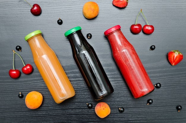 Three bottles of juice and fruits.