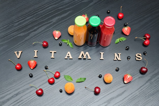Three bottles of juice, the inscription vitamins and fruits. wooden background.