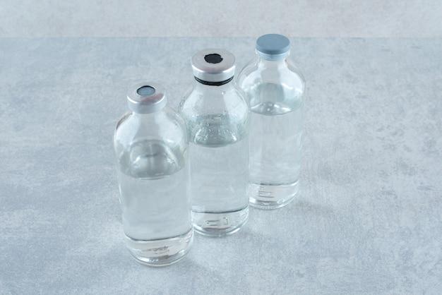 Tre bottiglie di etanolo medico sulla superficie grigia