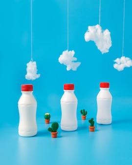 Tre bottiglie di latte, cactus e nuvole