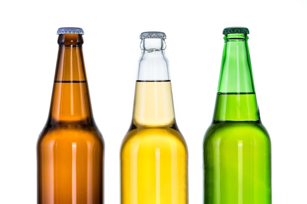 Три бутылки пива, изолированные на белой стене