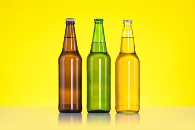 Три бутылки пива, изолированные на желтой поверхности