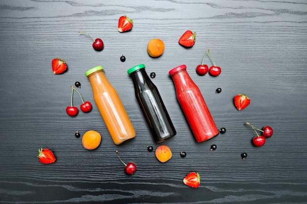 ジュースとフルーツの 3 つのボトル。黒の木製の背景。食のコンセプト