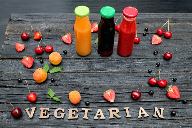 Three bottles with juice, fruit and inscription vegetarian on black wooden background. food concept