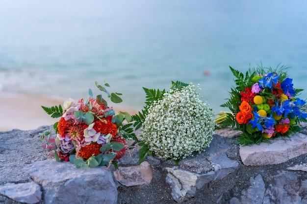 美しい色の結婚式からの花の3つの花束。地平線上の海
