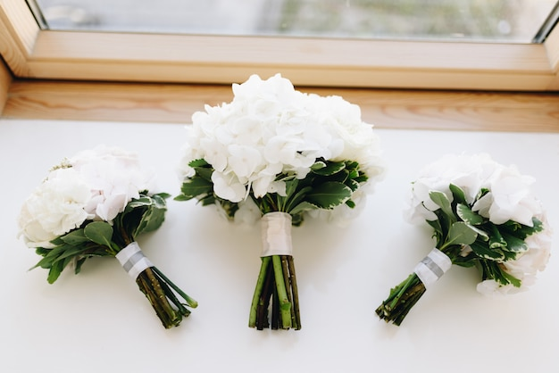 Three bouquets of white hydrangea lay flat on the window-sill top-down
