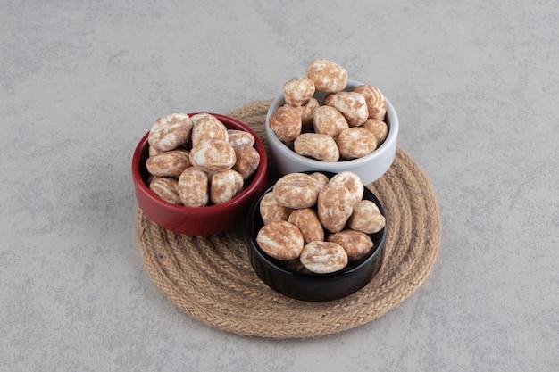 Tre scodelle di biscotti alla cannella sul sottopentola, sulla superficie del marmo