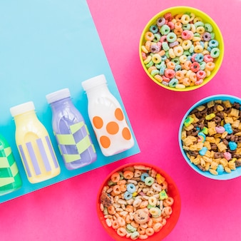 Three bowls of cereals with milk bottles