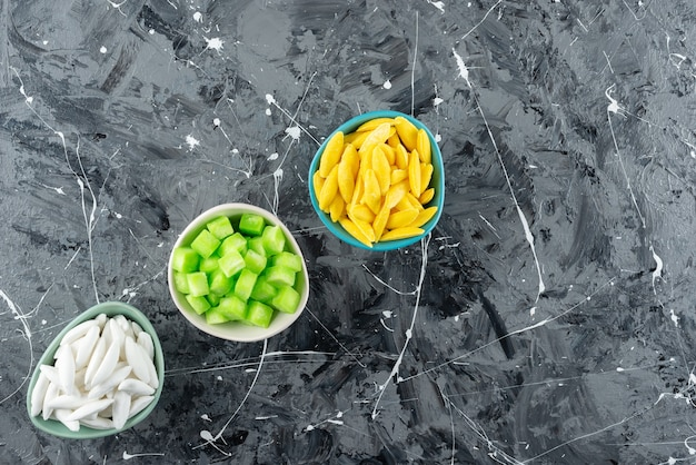 Three bowls full of colorful sweet candies on a marble background.