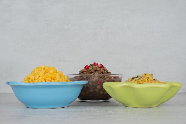 白いテーブルの上にゆでたトウモロコシ、スープ、豆の3つのボウル。