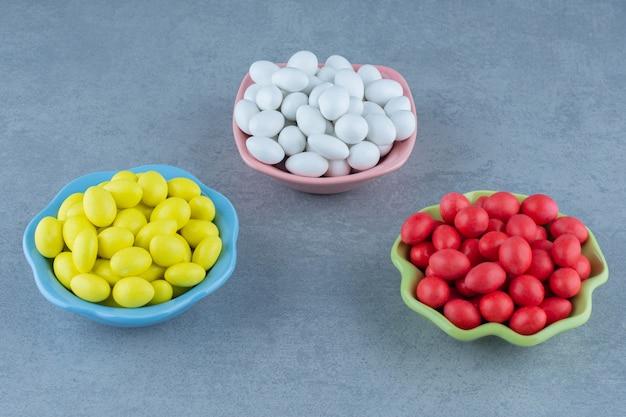 大理石のテーブルの上にチョコレートの3つのボウル。