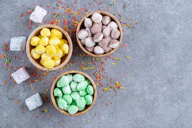 Три миски разноцветных конфет на мраморной поверхности