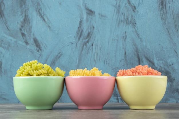 Три чаши красочных фузилли на мраморной поверхности.