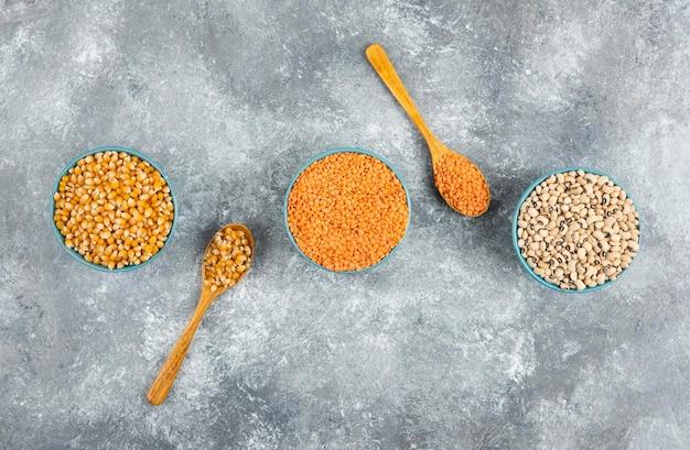 Три миски кукурузных зерен, бобов и красной чечевицы на мраморной поверхности.