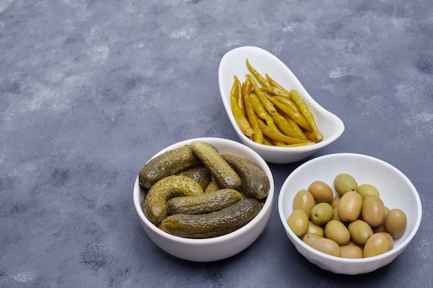 Три миски маринованных огурцов, перца и оливок на синем фоне.
