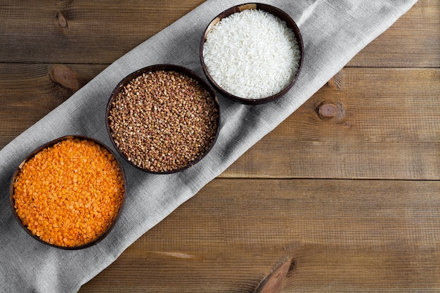 캔버스 냅킨 평면에 원시 곡물 메밀, 쌀, 렌즈 콩의 세 그릇은 나무 배경에 누워