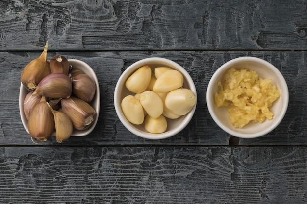 木製のテーブルの上に全体と加工されたニンニクの3つのボウル。キッチンに人気のスパイス。