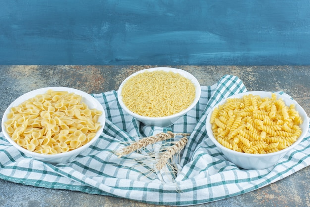Three bowls of pasta next to two wheat on the towel, on the marble background.