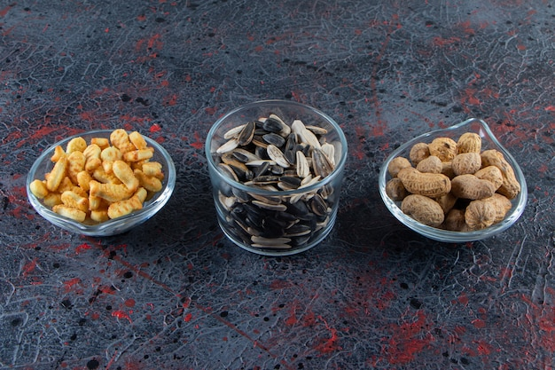Three bowls of peanuts, sunflower seeds and crackers on blue surface.