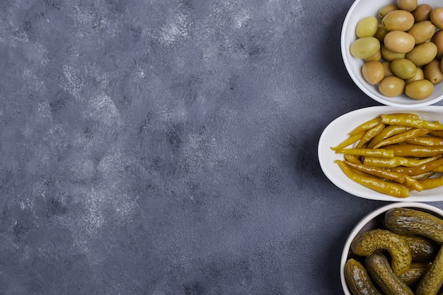 Three bowls of pickled cucumbers, peppers and olives on blue background.