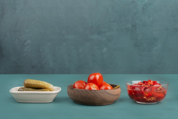 Three bowls of pickled red pepper, tomatoes and cucumbers on blue table.
