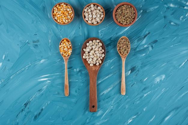 Tre ciotole di mais crudo, ceci e grano saraceno sulla superficie blu.