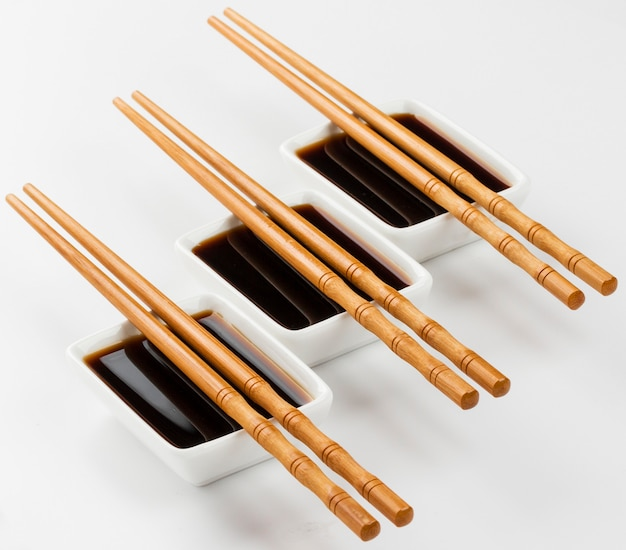Three bowls of soy sauce on white
