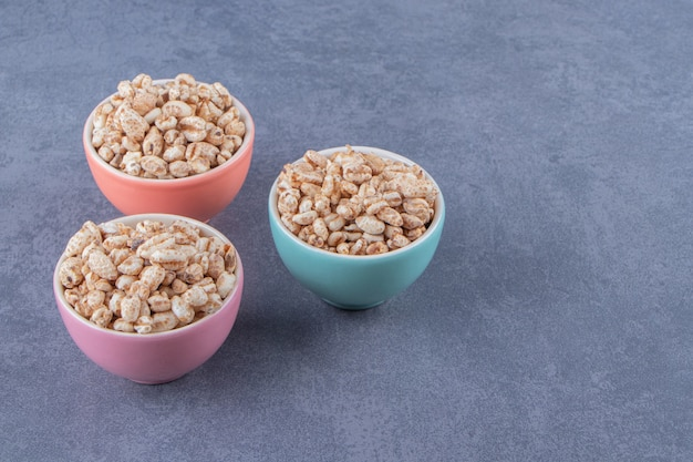 Three bowls of sweet muesli, on the marble background.