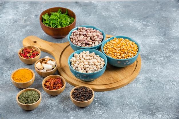 Tre ciotole di vari fagioli e semi con spezie su tavola di legno.
