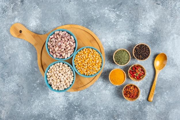 Tre ciotole di vari fagioli e semi su tavola di legno.