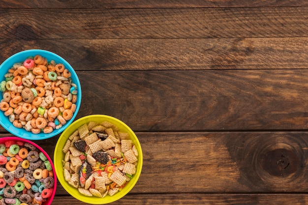 Three bowls with cereals on table