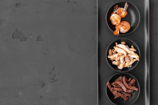 Three bowls with cooked beef chicken slices and prawns on black background