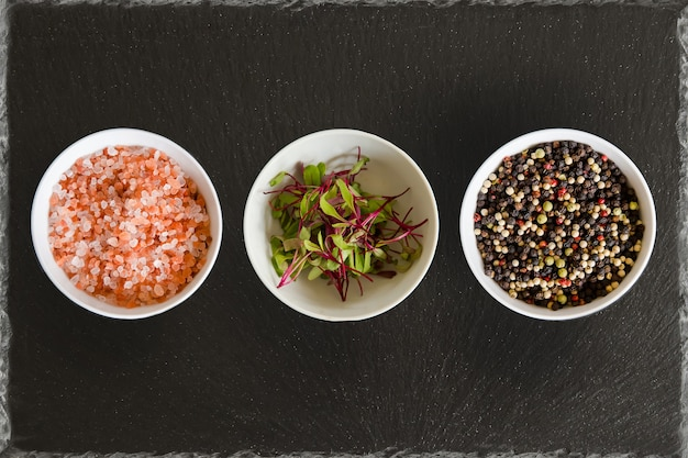 Three bowls with pepper salt and herbs