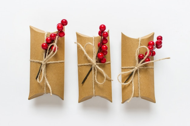 Три подарочные коробки обернуты веревкой и украшены ветками красных ягод на белом фоне.
