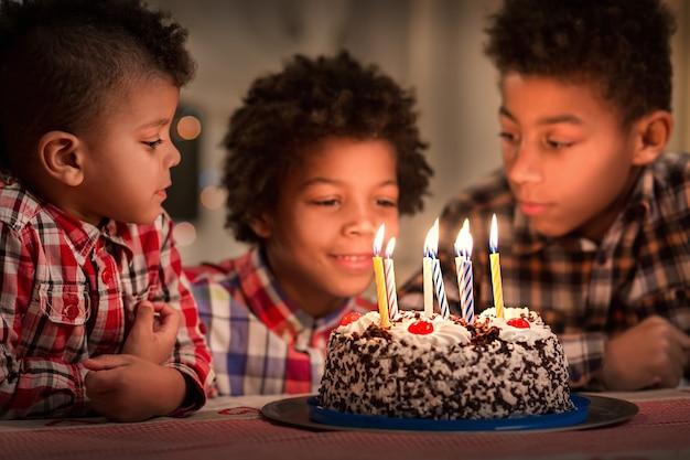 私たちの驚きを祝うために誕生日テーブルのお祝いの日に3人の男の子とバースデーケーキアフロキッズ...