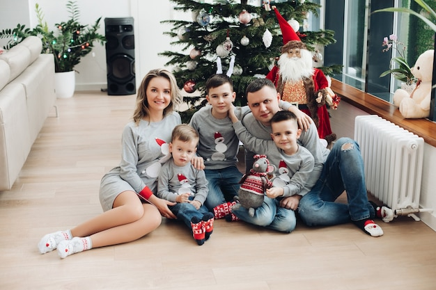 Three boys wearing same pullovers while posing on camera with their parents. holiday concept