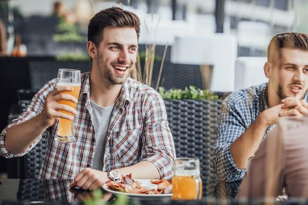 Трое мальчишек с пивом проводят свободное время в кафе.