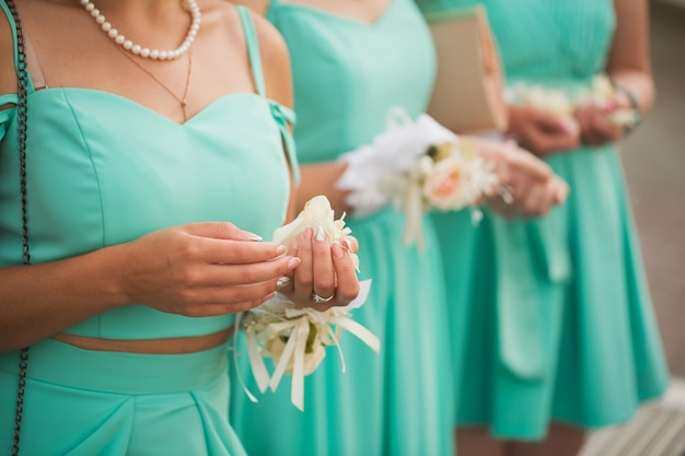 Three bridesmaids holding a wedding bouquet in hands