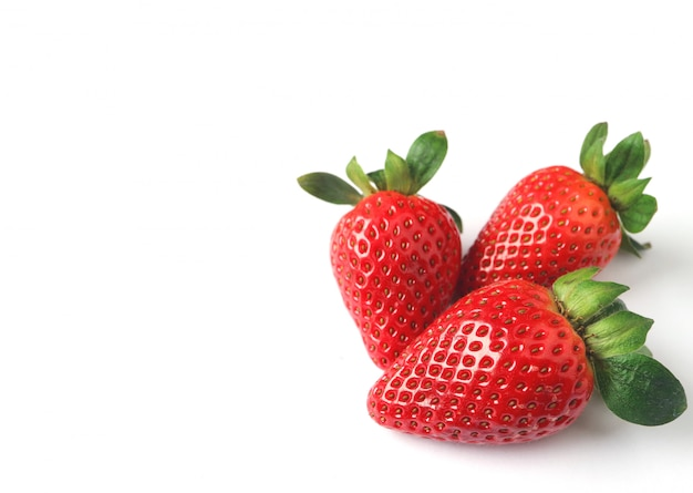 Three bright color red fresh ripe strawberries isolated on white background with free spac