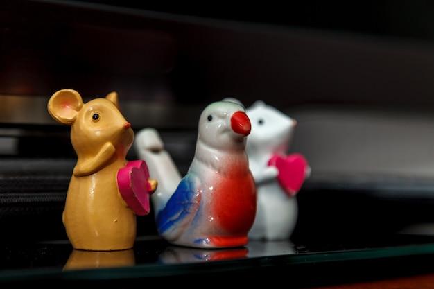 Три ярких разноцветных керамических игрушки. мышь с красным сердцем и птичка-свистулька между ними. ручной работы. поделки на полке с темным фоном. украшение дома. ручная работа, хобби, рукоделие