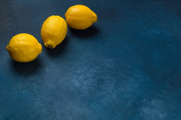 Three bright yellow citrus fruits on a blue background top view
