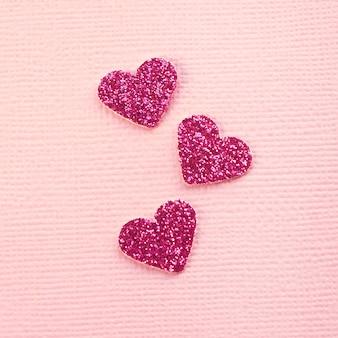 Три блестящих розовых сердечка хаотично лежат на розовом текстурном фоне. нравится концепция.