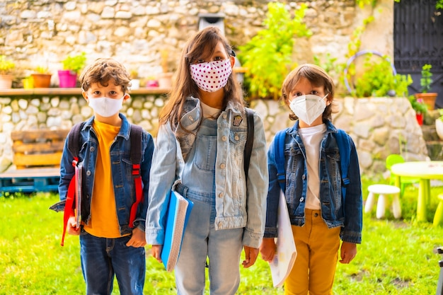 学校に戻る準備ができているフェイスマスクを持つ3人の兄弟の子供。新しい正常性、社会的距離、コロナウイルスのパンデミック、covid-19。