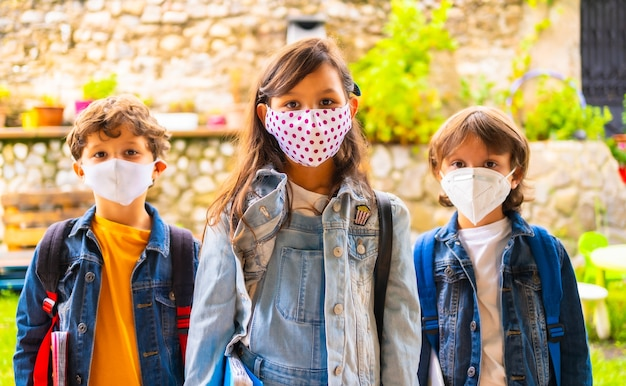 Three brother children with face masks ready for going back to school. new normality, social distance, coronavirus pandemic, covid-19.