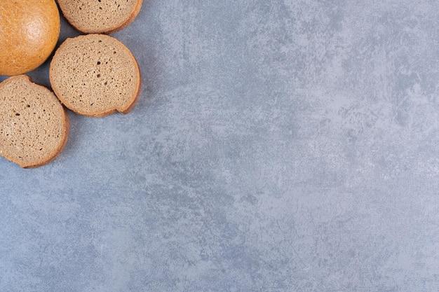 Три ломтика черного хлеба вокруг одной булочки на мраморном фоне. фото высокого качества