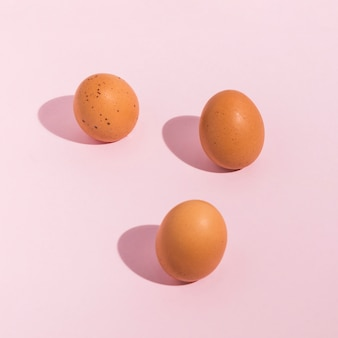 Three brown chicken eggs scattered on table