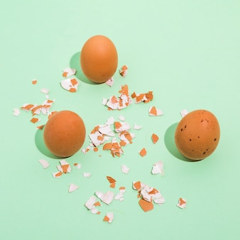 Three brown chicken eggs with broken shell on table