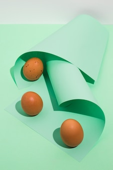 Three brown chicken eggs with green rolled paper