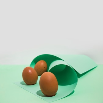 Three brown chicken eggs with rolled paper