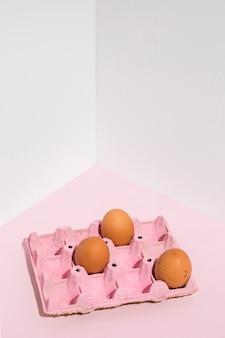 テーブルの上のピンクのラックに3つの茶色の卵